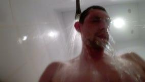 Mann wäscht seinen Kopf unter der Dusche stock video footage