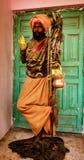 Mann warf auf einem Fuß auf, während er in der Farbe während Holi Festiva bedeckt wird lizenzfreies stockbild
