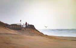 Mann wartet nahe roter Fahne an den Dünen stockbilder