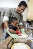 Mann-waschende Teller mit Sohn stockbilder