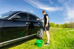 Mann-waschendes Auto auf dem Gebiet auf Sunny Day Lizenzfreie Stockbilder