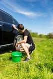 Mann-waschendes Auto auf dem Gebiet auf Sunny Day Stockfotografie