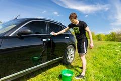Mann-waschendes Auto auf dem Gebiet auf Sunny Day Lizenzfreie Stockfotografie