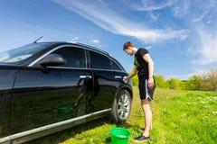 Mann-waschendes Auto auf dem Gebiet auf Sunny Day Lizenzfreies Stockbild