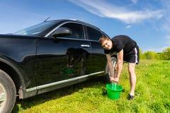 Mann-waschendes Auto unter Verwendung des Schwammes und Eimer auf dem Gebiet Stockfoto