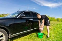 Mann-waschendes Auto unter Verwendung des Schwammes und Eimer auf dem Gebiet Lizenzfreie Stockfotos