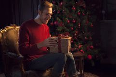 Mann wickelt ein Weihnachtsgeschenk ein Stockfotografie
