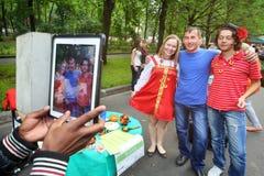 Mann wird mit Leuten in den russischen Volkskostümen fotografiert Lizenzfreie Stockfotos