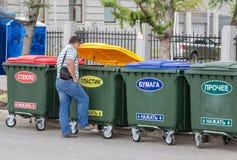 Mann wirft Abfall im Müllcontainer Stockbilder