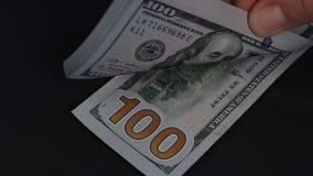 Mann wirft auf dem Tisch 100 Dollarscheine stock video footage