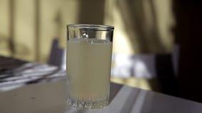 Mann wirft schäumende Tablette in ein Glas Wasser am Tisch stock video