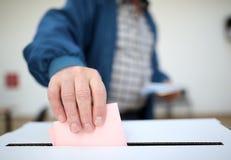 Mann wirft seinen Stimmzettel an den Wahlen Lizenzfreies Stockfoto