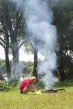 Mann zündet ein Feuer nahe dem Fluss an. Stockbilder