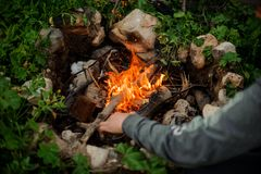 Mann zündet Feuer in einem touristischen Lager an lizenzfreies stockfoto