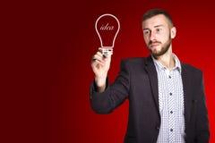 Mann zeichnet eine Glühlampe Lizenzfreies Stockfoto