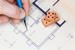 Mann zeichnet einen Hausplan Stockbilder