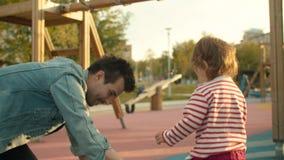 Mann zeichnet mit Kreiden auf dem Spielplatz stock video footage