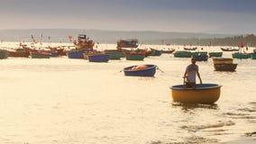 Mann zeichnet ringsum vietnamesisches Fischerboot zum Meer stock video