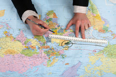Mann zeichnet vom Plan auf der Weltkarte Lizenzfreies Stockbild