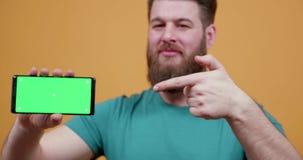 Mann zeigt stolz sein Telefon mit grünem Schirm an stock video footage