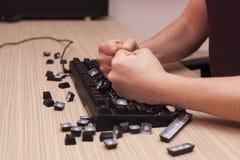 Mann zertrümmert eine mechanische Computertastatur in der Raserei unter Verwendung beider Fäuste Lizenzfreie Stockfotografie