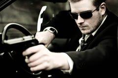 Mann zieht ein Gewehr im Auto Stockfotografie