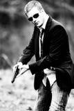 Mann zieht ein Gewehr im Auto Stockbilder