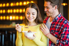 Mann zieht Frau im Café ein stockfoto
