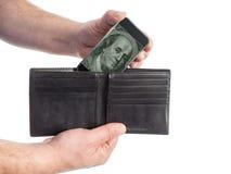 Mann zieht Smartphone, das Bargeld von seiner Geldbörse enthält Lizenzfreie Stockbilder