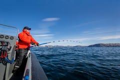 Mann zieht vom Seefisch aus Angelrutenbiegungen Rote Jacke sport Lizenzfreie Stockfotos