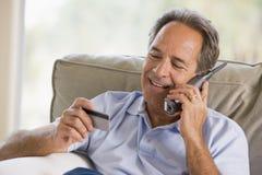 Mann zuhause unter Verwendung des Telefons, das Kreditkarte betrachtet Stockfotografie