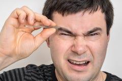 Mann zupft Augenbrauen mit Pinzette lizenzfreie stockfotografie