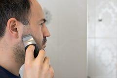Mann-Zutat-Bart im Badezimmer mit elektrischem Rasierapparat Lizenzfreies Stockbild