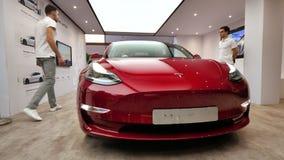 Mann zwei nahe Luxuselektroauto des roten Sports des Tesla Model 3 stock footage