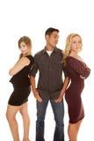 Mann zwischen dem Blick mit zwei Frauen zur Seite Lizenzfreies Stockbild
