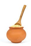 Manna croup. In a clay pot with a wooden spoon on a white background Royalty Free Stock Images