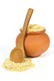 Manna croup. In a clay pot with a wooden spoon on a white background Stock Images