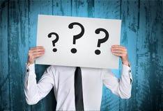 Mannabdeckungsgesicht mit Fragenbrett Lizenzfreies Stockbild