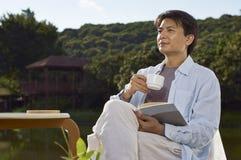 Mannablesen im Freien mit Kaffee in der Hand Stockbild