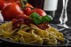 Mannagrynpasta med kryddig tomatsalsa, vitlök och basilika Arkivbild