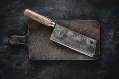 Mannaia rustica di carne e del tagliere su fondo scuro fotografia stock