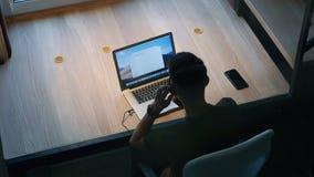 Mannarbeiten über den Laptop, der durch die Tabelle sitzt Innenministeriumkonzept Rückseitige Ansicht stock footage