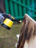 Mannarbeiten im Freien Mann, der hölzerne Bretter mit Gasbrenner brät Stockfoto