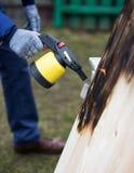Mannarbeiten im Freien Mann, der hölzerne Bretter mit Gasbrenner brät Stockbilder