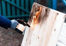 Mannarbeiten im Freien Mann, der hölzerne Bretter mit Gasbrenner brät Stockbild