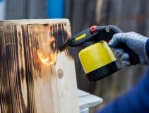 Mannarbeiten im Freien Mann, der hölzerne Bretter mit Gasbrenner brät Lizenzfreie Stockfotos