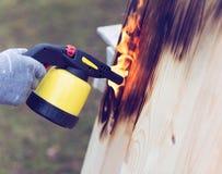 Mannarbeiten im Freien Mann, der hölzerne Bretter mit Gasbrenner brät Lizenzfreies Stockbild