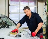 Mannarbeitskraft auf einer Waschanlage stockbilder