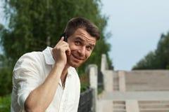 Mannaufruf durch Telefon im Sommerparkblick auf Kamera Stockbilder