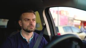 Mannautofahren, nach einer Parkmöglichkeit suchend stock video